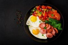 Oeufs au plat avec la saucisse et les légumes dans une poêle sur un fond noir dans le style rustique Photos libres de droits