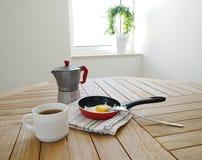 Oeufs au plat avec le pot de café sur la table Photo stock