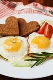 Oeufs au plat avec les légumes frais et pain grillé dans la forme du coeur du plat blanc Images stock
