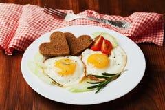 Oeufs au plat avec les légumes frais et pain grillé dans la forme du coeur du plat blanc Image libre de droits