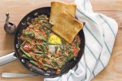 Oeufs au plat avec les légumes mélangés dans une poêle images libres de droits