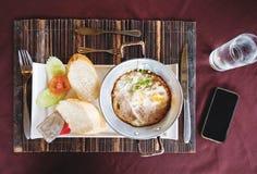 Oeufs au plat casserole et pain de petit déjeuner, avec l'eau et le smartphone, vue supérieure Images stock