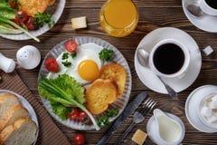 Oeufs au plat, croûtons et salade avec du café et le jus d'orange photographie stock