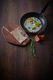 Oeufs au plat dans une poêle Avec des tomates et des oignons verts Sur une planche à découper, et sur un fond foncé Déjeuner sain Images libres de droits