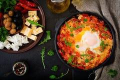 Oeufs au plat de petit déjeuner avec les légumes - shakshuka dans une poêle sur un fond noir dans le style turc Photographie stock libre de droits