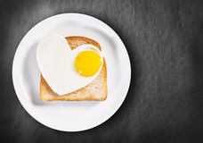Oeufs au plat en forme de coeur et pain grillé frit Photographie stock