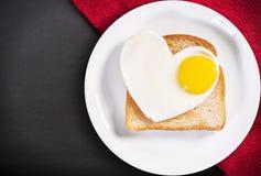 Oeufs au plat en forme de coeur et pain grillé frit Image stock