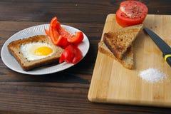 Oeufs au plat en pain avec des légumes sur la table images stock