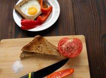 Oeufs au plat en pain avec des légumes sur la table photographie stock