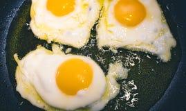 3 oeufs au plat faisant frire dans une casserole avec l'huile d'olive images stock