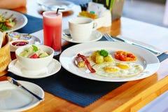 Oeufs au plat, salade de fruits et jus frais Image stock
