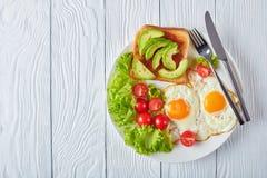 Oeufs au plat, salade fraîche, pain grillé d'un plat image stock