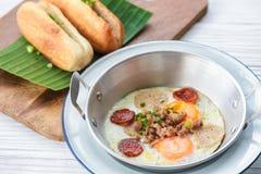 Oeufs au plat sur la casserole avec du pain pour le petit déjeuner Image libre de droits