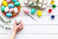 Oeufs avec la peinture colorée pour la tradition de Pâques sur la maquette en bois blanche de vue supérieure de fond photographie stock