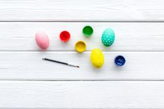 Oeufs avec la peinture colorée pour la tradition de Pâques sur la maquette en bois blanche de vue supérieure de fond photos stock