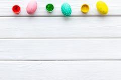 Oeufs avec la peinture colorée pour la tradition de Pâques sur la maquette en bois blanche de vue supérieure de fond image stock