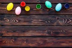 Oeufs avec la peinture colorée pour la tradition de Pâques sur la maquette en bois de vue supérieure de fond photo libre de droits