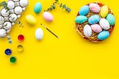 Oeufs avec la peinture colorée pour la tradition de Pâques sur la maquette jaune de vue supérieure de fond photos libres de droits