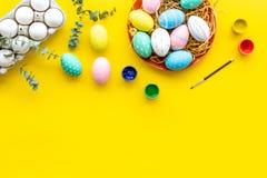 Oeufs avec la peinture colorée pour la tradition de Pâques sur la maquette jaune de vue supérieure de fond photos stock