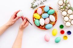 Oeufs avec la peinture colorée pour la tradition de Pâques sur la vue supérieure de fond blanc image libre de droits
