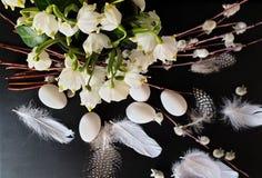 Oeufs avec le saule et plumes jaunes d'assiette creuse de ressort de fleur de bouquet toujours de vert rose blanc de la vie en ba photographie stock