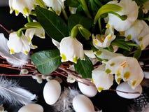 Oeufs avec le saule et plumes jaunes d'assiette creuse de ressort de fleur de bouquet toujours de vert rose blanc de la vie en ba photographie stock libre de droits
