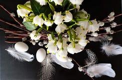 Oeufs avec le saule et plumes jaunes d'assiette creuse de ressort de fleur de bouquet toujours de vert rose blanc de la vie en ba image stock