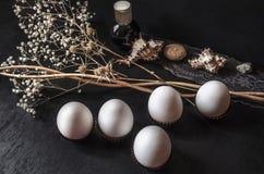 Oeufs blancs avec les fleurs sèches, la petite bouteille noire et les coquillages sur le ruban à jour Photos libres de droits