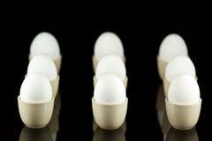 Oeufs blancs dans des coquetiers sur le noir 4 Photo libre de droits