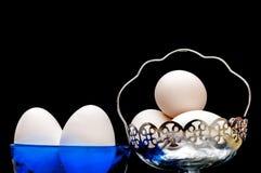 Oeufs blancs dans le bol en verre, panier, BG allumée, d'isolement, noire avant Photographie stock libre de droits