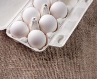 Oeufs blancs dans un paquet sur un fond de tissu Photo libre de droits
