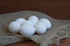 Oeufs blancs de poulet sur un textile non tissé sur un fond brun en bois photo libre de droits