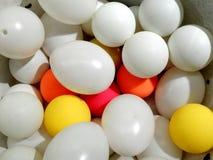 Oeufs blancs et boules en plastique de couleur différente s'étendant ensemble photographie stock libre de droits