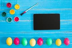 Oeufs, brosse et peinture colorés de pâques sur le fond de conseil en bois avec l'espace Photo stock