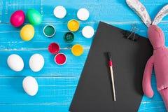 Oeufs, brosse et peinture colorés de pâques sur le fond de conseil en bois avec l'espace Image libre de droits