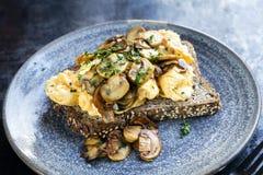 Oeufs brouillés et champignons de couche sur le pain grillé Photographie stock libre de droits
