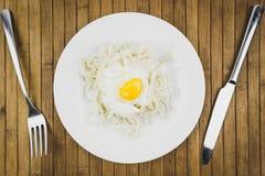 Oeufs brouillés et spaghetti dans les plats, les couteaux et la fourchette sur la table en bois photo libre de droits