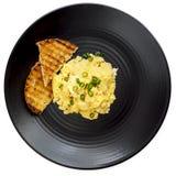 Oeufs brouillés et pain grillé sur la vue supérieure de plat noir d'isolement sur Whi Image stock