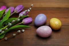 Oeufs colorés avec des tulipes sur le fond en bois Pâques, vacances de ressort photo libre de droits