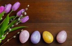 Oeufs colorés avec des tulipes sur le fond en bois Pâques, vacances de ressort image libre de droits