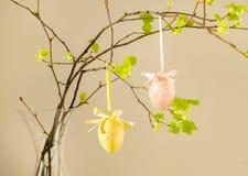Oeufs colorés avec les feuilles fraîches sur le fond rose Pâques, vacances de ressort image stock