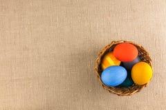 Oeufs colorés dans le panier, préparé pour les vacances de Pâques Photo stock