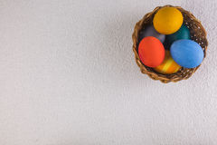 Oeufs colorés dans le panier, préparé pour les vacances de Pâques Photos stock