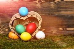 Oeufs colorés de Pâques dans la boîte en bois de coeur Photographie stock