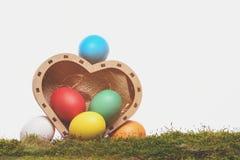 Oeufs colorés de Pâques dans la boîte en bois de coeur d'isolement sur le blanc Image libre de droits