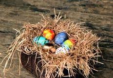 Oeufs colorés de Pâques dans le nid sur le fond en bois Images stock