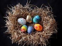 Oeufs colorés de Pâques dans le nid sur le fond noir Photos stock
