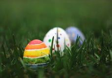 Oeufs colorés de Pâques sur le fond d'herbe verte Photographie stock