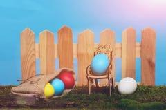 Oeufs colorés peints de Pâques à la barrière en bois sur la mousse verte Photographie stock libre de droits