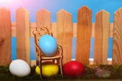 Oeufs colorés peints de Pâques à la barrière en bois sur la mousse verte Photo libre de droits